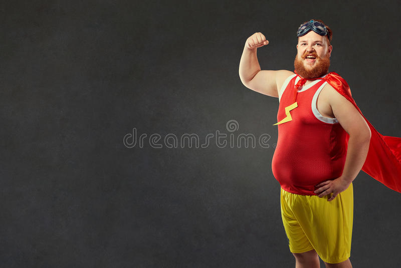 Een grappige vette mens in een superherokostuum stock afbeeldingen