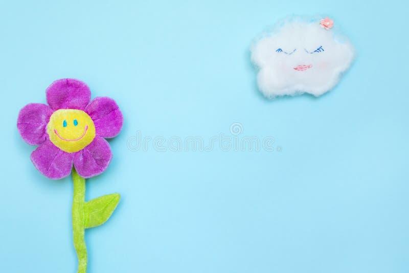 Een grappige wolk op een blauwe document achtergrond en een stuk speelgoed bloeien met een het glimlachen gezicht Foto's op het t royalty-vrije stock foto's