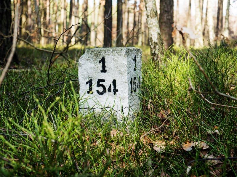 Een grenspost met een teken in het bos stock afbeelding