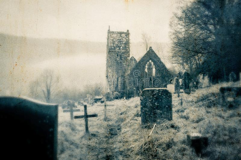 Een griezelig, verlaten kerkhof met een geruïneerde kerk op de achtergrond Met vaag, geeft de wijnoogst, grunge uit royalty-vrije stock fotografie