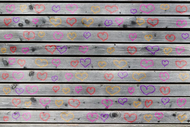 Een grijze houten muur met vele gekleurde harten stock afbeeldingen