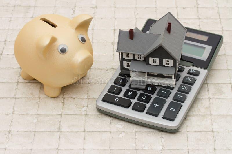 Een grijze huis, een spaarvarken en een calculator op steenachtergrond stock afbeelding