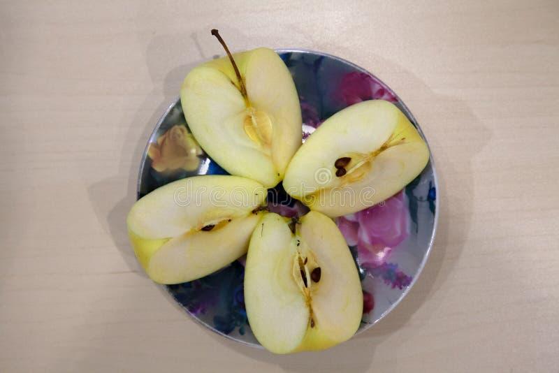 Een groene appelbesnoeiing in vier stukken op een gekleurde plaat na harv royalty-vrije stock foto's