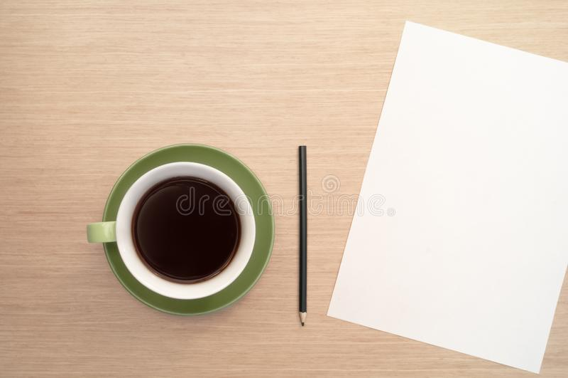 Een groene kop van koffie op de achtergrond van een lijst en een wit shee en een potlood stock fotografie