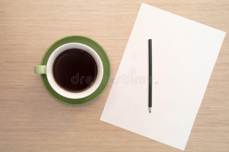Een groene kop van koffie op de achtergrond van een lijst en een wit shee en een potlood royalty-vrije stock foto