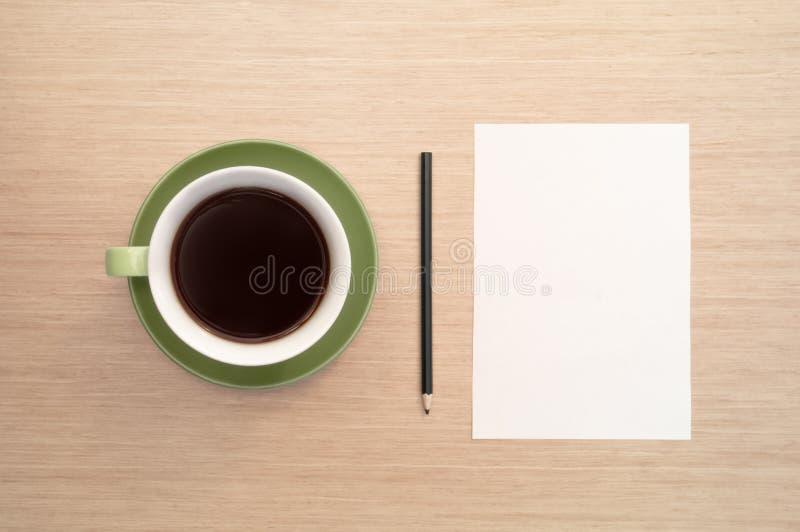 Een groene kop van koffie op de achtergrond van een lijst en een wit shee en een potlood stock foto