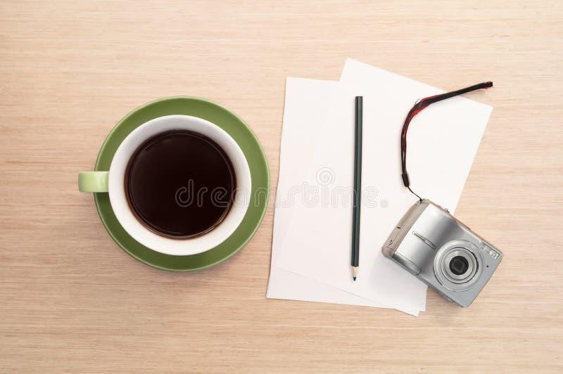 Een groene kop van koffie op de lijst en het lege blad, potlood, camera stock foto