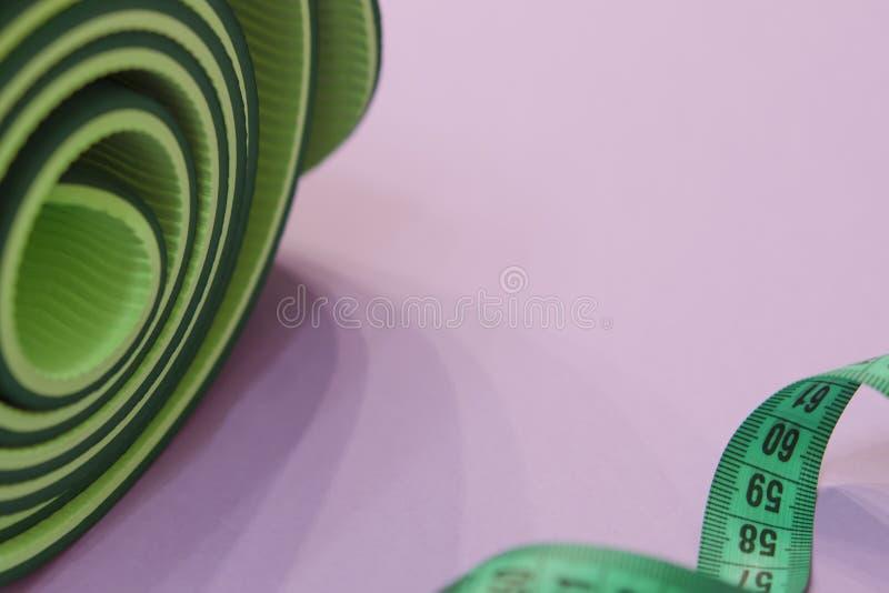 Een groene metende band verdraaide in een spiraal en een mat voor fitne stock afbeelding