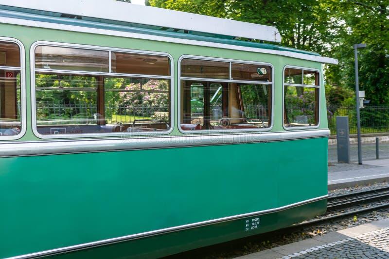 Een groene tandradbaanauto die zich op de sporen bij de bushalte bevinden stock foto's
