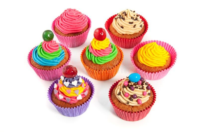 Een groep afgeroomd kleurrijk verfraaid cupcakes stock afbeeldingen
