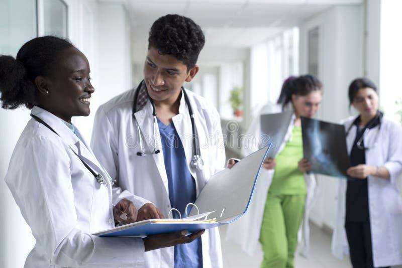 Een groep artsen met gemengde rassen Jongeren in witte jassen, die in de ziekenhuisgang staan, glimlachen, houden medische zorg v royalty-vrije stock fotografie