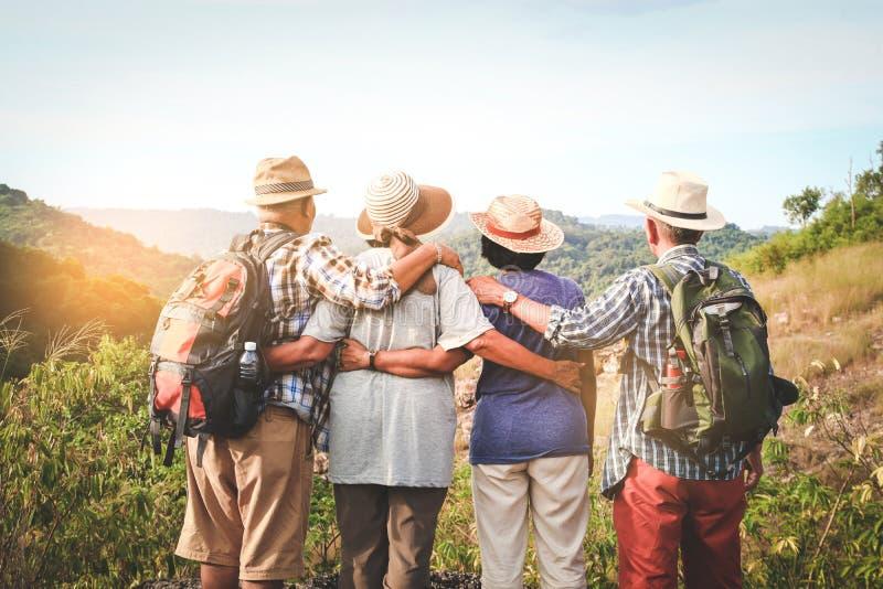 Een groep Aziatische ouderen die op hoge bergen klimmen en staan royalty-vrije stock foto's