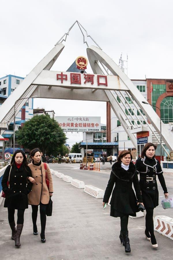 Een groep Aziatische vrouwen in lange lagen die over de brug over de Rode Rivier van Hekou, de achtergrond van China aan Lao Cai  royalty-vrije stock fotografie