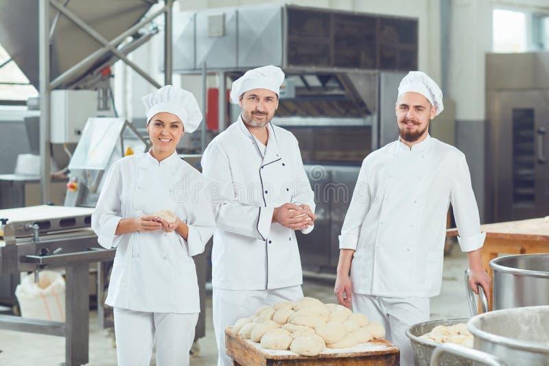 Een groep bakkers glimlacht bij de bakkerij royalty-vrije stock fotografie