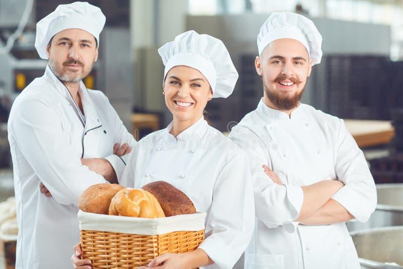 Een groep bakkers glimlacht bij de bakkerij royalty-vrije stock foto's