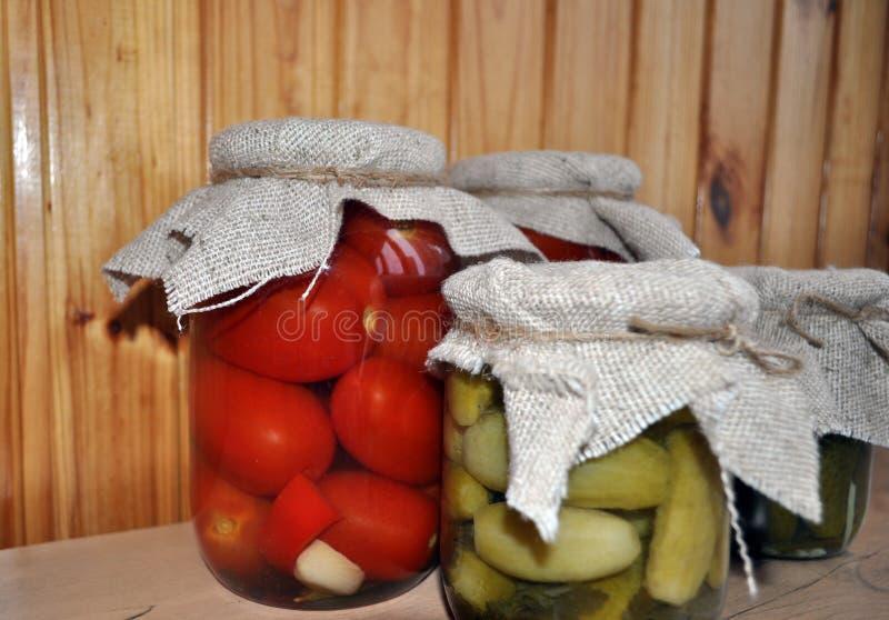 Een groep blikken met ingeblikte tomaten en komkommers stock fotografie
