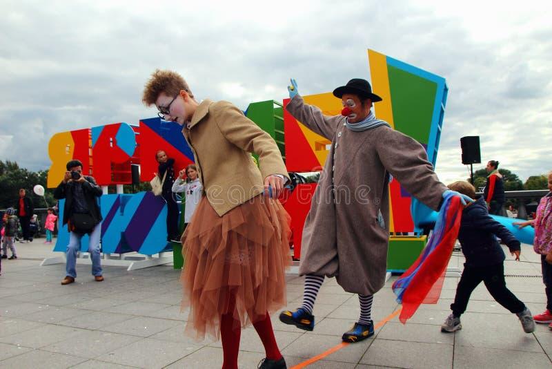 Een groep clowns, pret-houdende van kinderen, op de dag van de stad van Moskou stock afbeelding