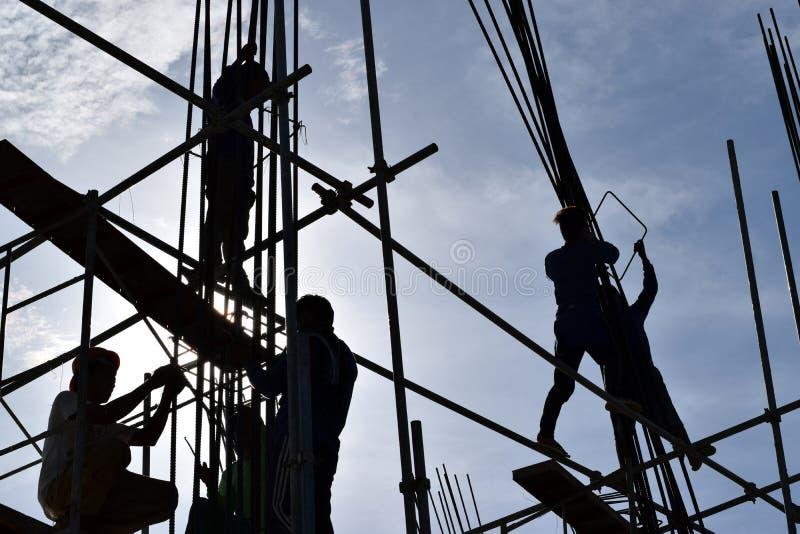 Een groep de Filipijnse arbeiders die van het Bouwstaal staalbars bij high-rise de bouw zonder juiste beschermende kostuums en sa royalty-vrije stock foto