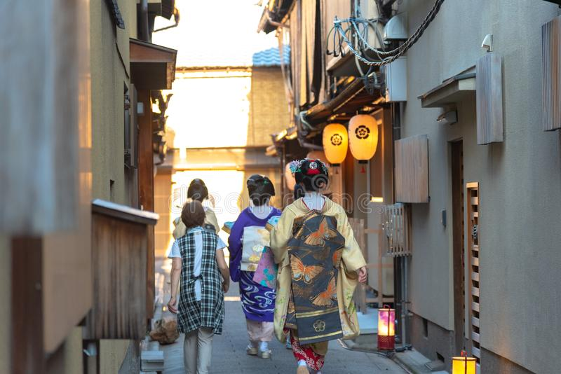 Een groep die geisha en maiko traditionele kledingskimono dragen die op straat lopen royalty-vrije stock foto