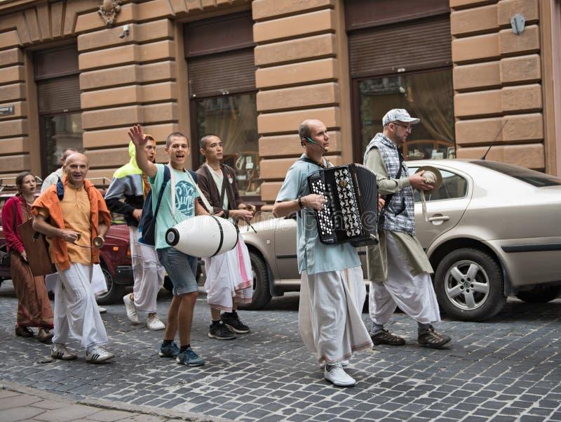 Een groep die hazen Krishnas het zingen trekken door de oude stad van Lviv, de Oekraïne royalty-vrije stock fotografie