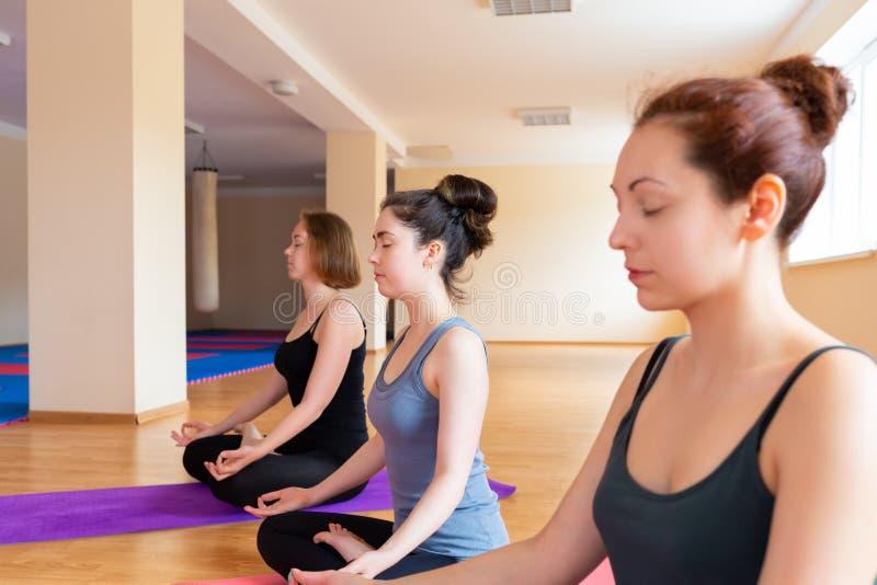 Een groep die jonge vrouwen die yoga in het klaslokaal doen, meditatie doen Het concept sporten, aerobics en yogapraktijk stock foto