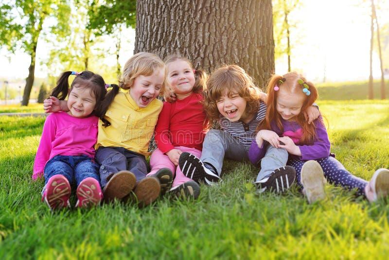 Een groep die kleine kinderen in kleurrijke kleren zitting op het gras omhelzen onder een boom in een en park die lachen glimlach royalty-vrije stock afbeelding