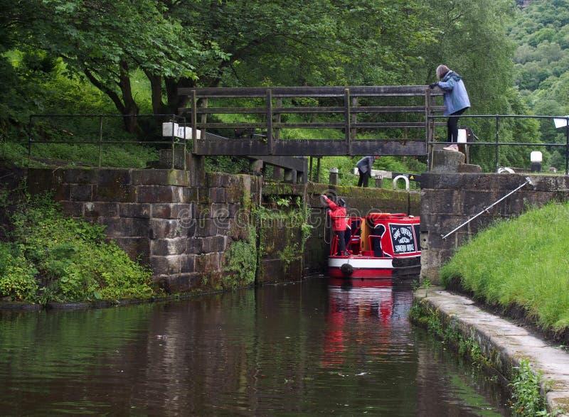 Een groep die mensen een narrowboat neemt hoewel een sluisdeur op het rochdalekanaal binnen brug West-Yorkshire hebden stock foto