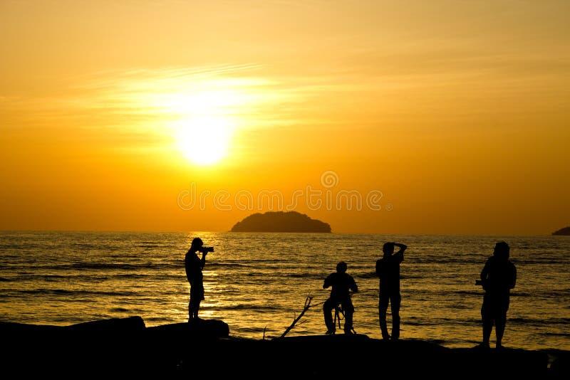 Een groep fotografen in actie tijdens een zonsondergang in het strand van Tanjung Aru stock afbeeldingen