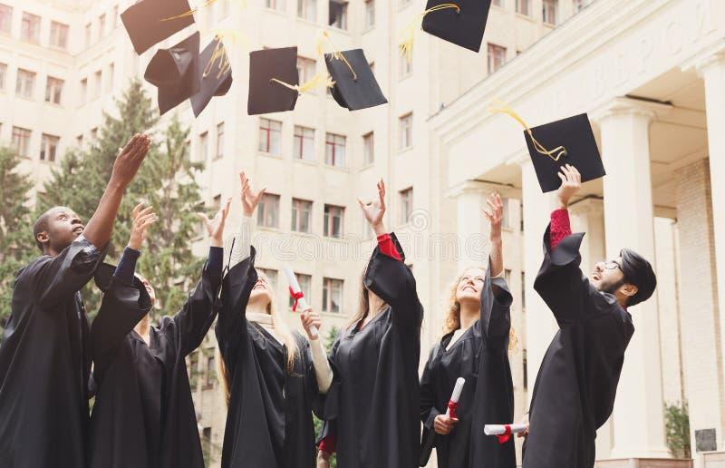 Een groep gediplomeerden die graduatiekappen in de lucht werpen stock afbeelding