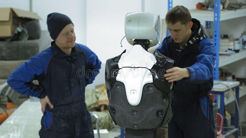 Een groep ingenieurs creeert een moderne robot of androïde Controle en reparatie gebroken punten Vervaardiging en vervaardiging v royalty-vrije stock foto's
