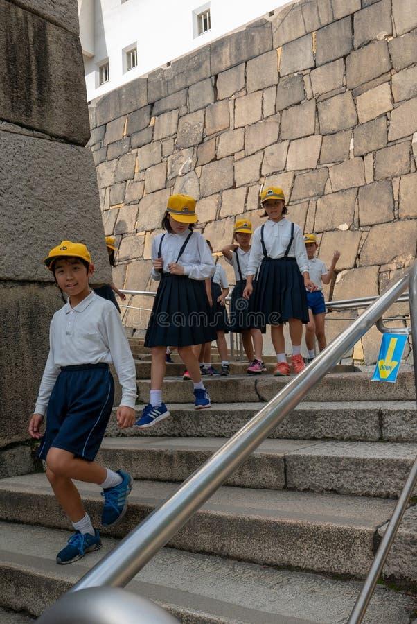 Een groep Japanse schoolkinderen daalt van Osaka Castle Complex in de herfstseizoen in Osaka, Japan royalty-vrije stock fotografie