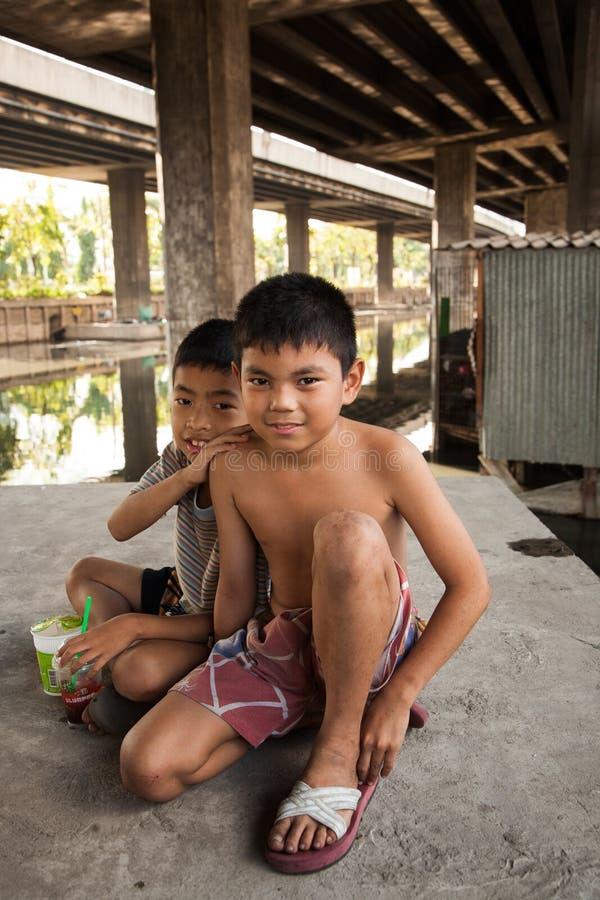 Een groep jonge jongens heeft samen pret in de krottenwijk van Klong Toey in Bangkok stock foto's