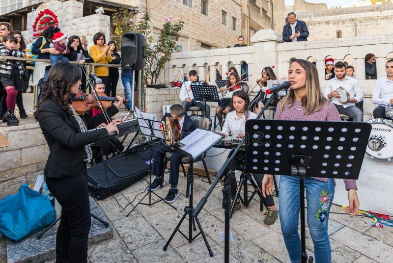 Een groep jonge kunstenaars voert Kerstmisliederen op het vierkant dichtbij de Kerstboom in de stad van Nazareth-stad in Israël u royalty-vrije stock foto