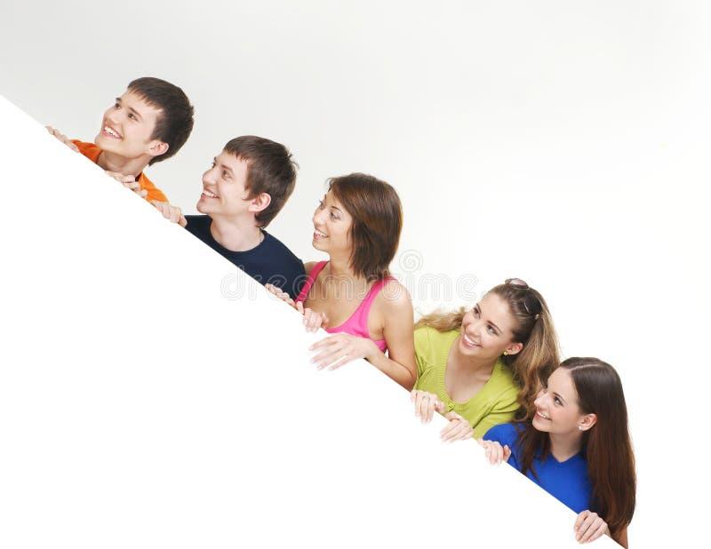 Een groep jonge tieners die een witte banner houden stock afbeelding