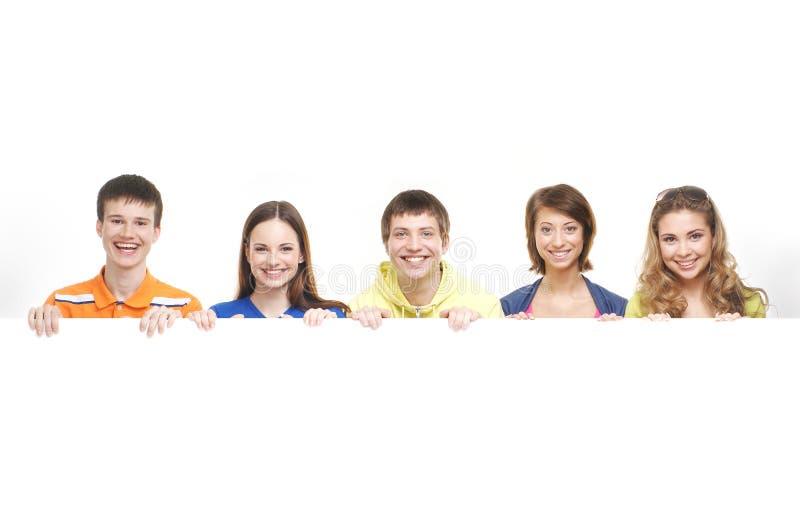 Een groep jonge tieners die een witte banner houden stock fotografie