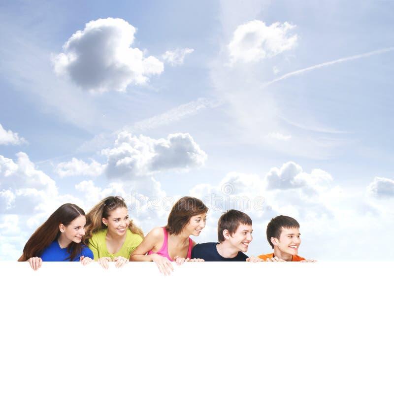 Een groep jonge tieners die een witte banner houden royalty-vrije stock foto