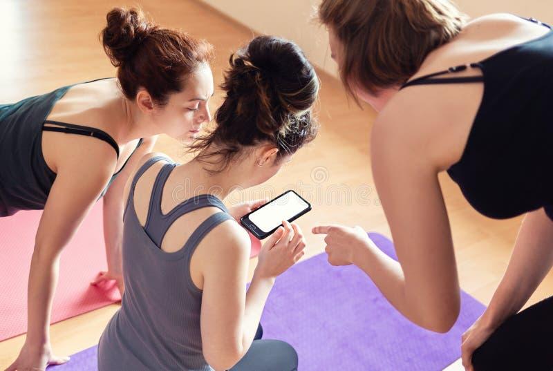 Een groep jonge vrouwen bekijkt de telefooninformatie over de opleiding Hoogste mening van de rug Concept moderne technologieën, royalty-vrije stock afbeeldingen
