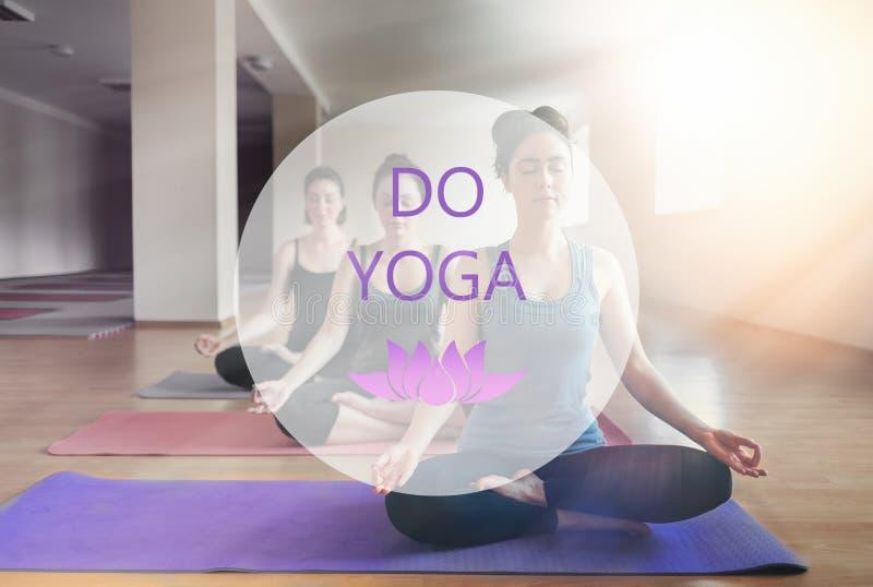 Een groep jonge vrouwen die yoga in het klaslokaal doen Het concept sporten, meditatie en yogapraktijk De tekst DOET YOGA royalty-vrije stock foto