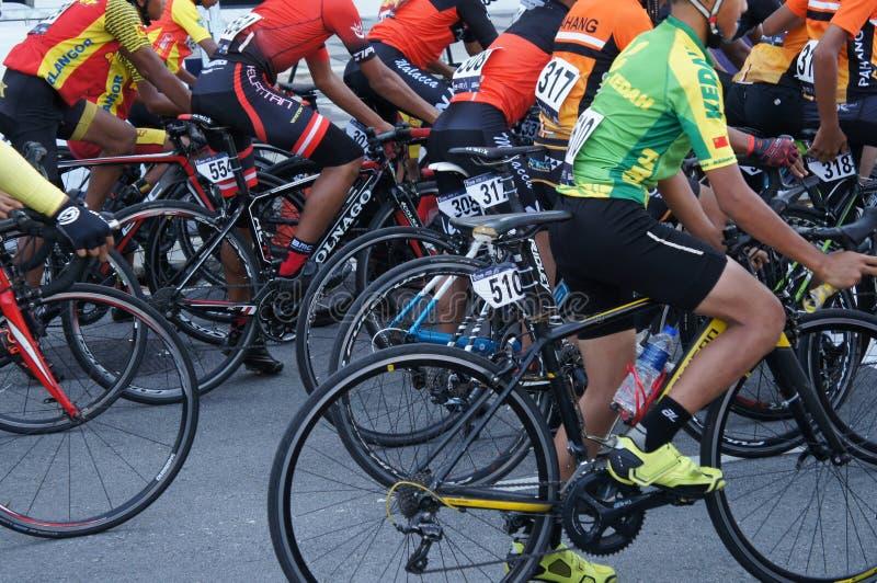 Een groep jongens kleedde zich in het cirkelen van sporten samen met hun fietsen stock foto