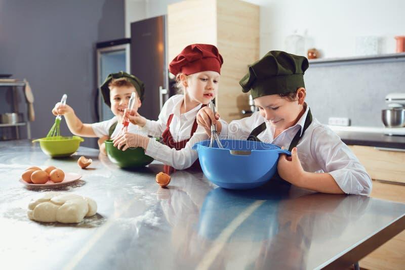 Een groep kinderen kookt bij de lijst in de keuken stock foto's
