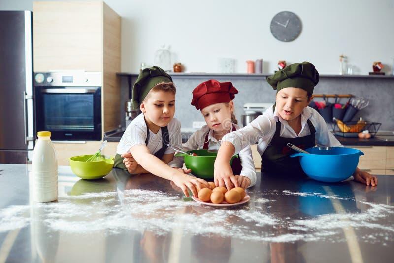 Een groep kinderen kookt in de keuken royalty-vrije stock afbeelding