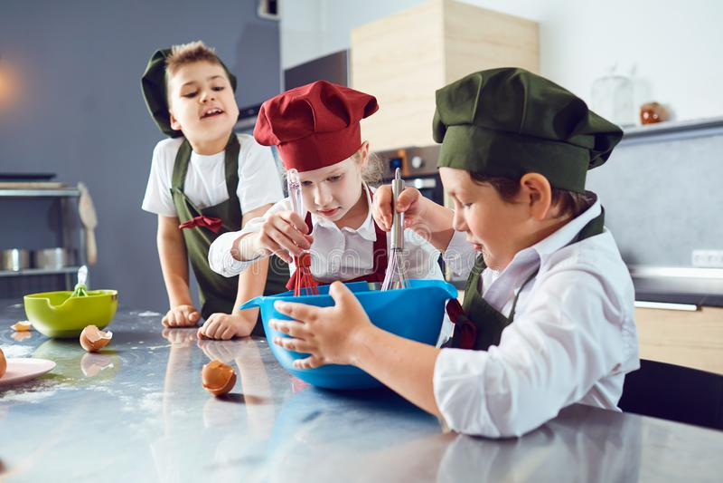 Een groep kinderen kookt in de keuken stock afbeeldingen