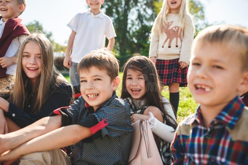 Een groep kinderen van school en de peuterleeftijd zitten op het groene gras in het park stock afbeeldingen