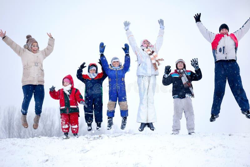 Een groep kinderen, vrouwen en mannen die in de lucht bij sneeuww springen royalty-vrije stock fotografie