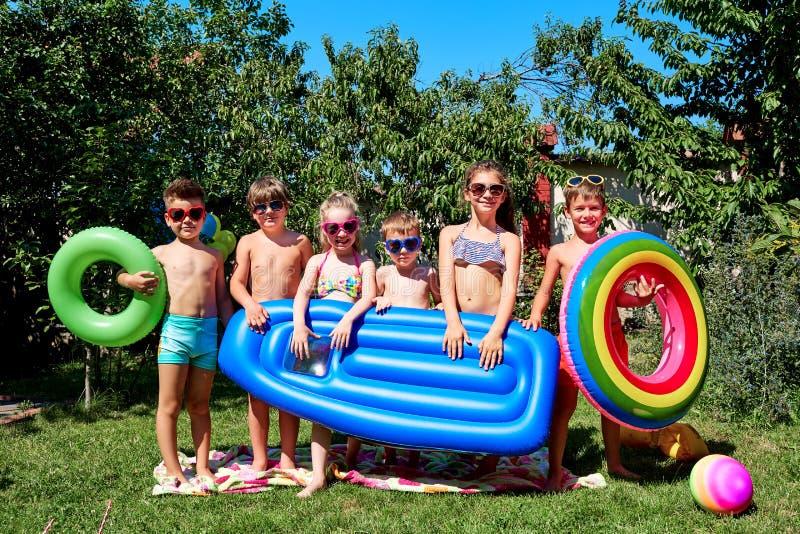 Een groep kinderen in zwempakken in de zomer stock afbeeldingen