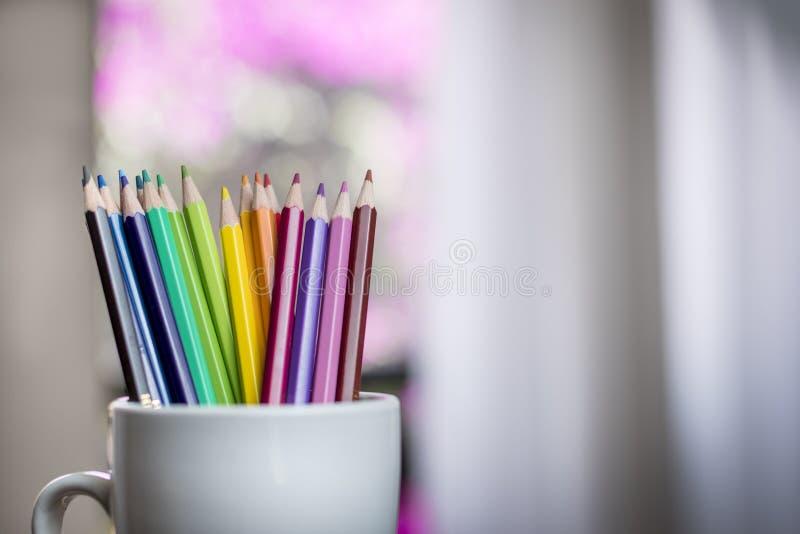 Een groep kleurenpotloden in een witte kop royalty-vrije stock afbeeldingen