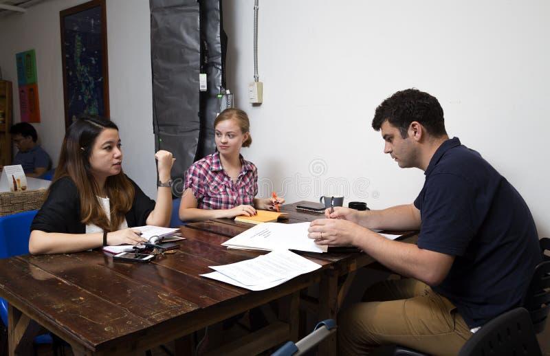 Een groep mensen bespreekt ideeën in een koffie, toevallige commerciële vergadering stock afbeelding