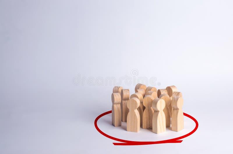Een groep mensen bevindt zich in een cirkel op een witte achtergrond Houten cijfers Gemeenschap, partij Statistieken en de publie stock foto's