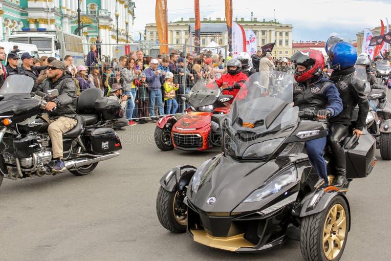 Een groep motorrijders gaat door toeschouwers over stock afbeeldingen