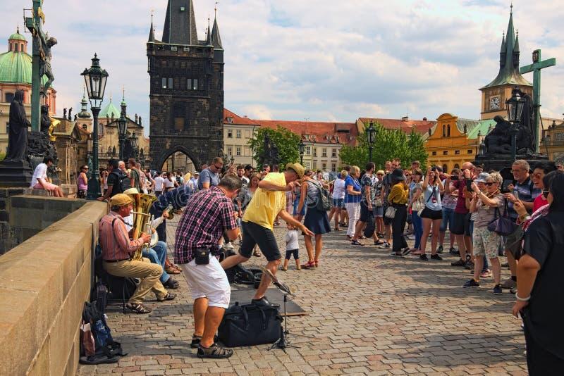 Een groep musici voert een lied met een tapdans op Charles Bridge in Praag uit Bewolkte de zomerdag stock afbeeldingen
